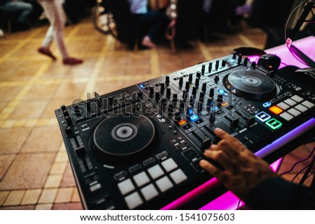 DJ turntable console mixer controlling with hand in concert nightclub stage