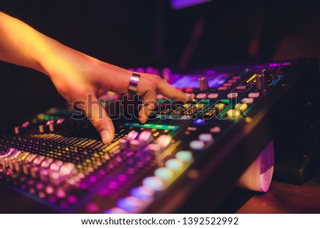 DJ turntable console mixer controlling with two hand in concert nightclub stage.
