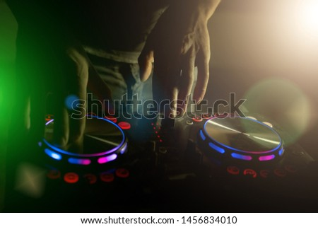 DJ turntable console mixer controlling with two hand in concert nightclub stage. . Music is awesome.