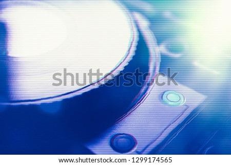 DJ turntable edited with glitch effect in blue stage lights.Concert disc jockey audio equipment in night club.Play digitial music on rave party