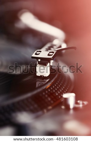 Dj turntable playing vinyl record with music. Focus on turntables needle playing musical records.Audio equipment for pro disc jockey.Disc jockey pro equip.Instagram like filter light leak
