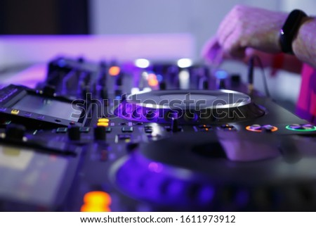 Dj turntable & sound mixer on stage in nightclub.Professional disc jockey plays music set in night club.Top level audio equipment on concert.focus on djs hands and turntables with illuminated buttons