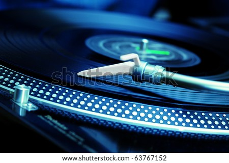 DJ turntable vinyl record player playing analog record disc with hip hop or club music in the nightclub at party or concert. Audio equipment for disc jockey