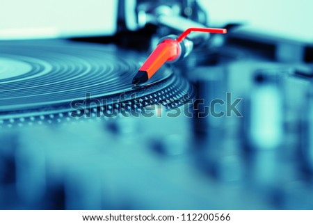 DJ turntable vinyl record player playing analog record with music.Blue color.Disc jockey audio equipment for concert,disc jockey,night club party,sound recording studio.Hifi technology.Focus on needle
