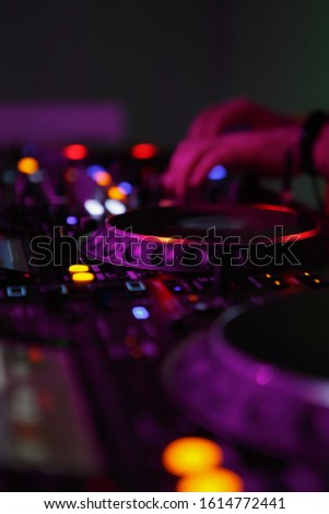 Dj turntables and sound mixer on stage.Professional disc jockey mixes musical tracks on techno party in night club.Vertical background with musician mixing music on rave festival