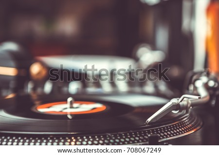 Dj vinyl records player with music disc.Turntables at hip hop party in night club.Professional hi-fi turn table equipment for disc jockey to play musical tracks on concert stage.Vintage djs gear