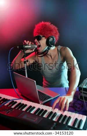 Dj with colorful light and music mixing digital equipment