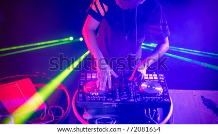DJ with headphones playing music  at night club party on light background
