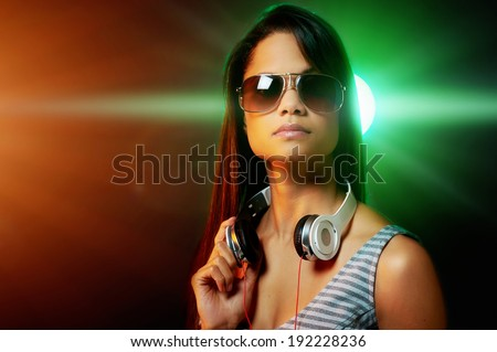 DJ woman portrait with headphones and nightclub lights