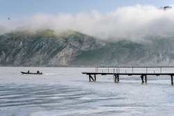 Djerdap, Serbia - June 8, 2019. Djerdap National Park landscape with morning fog above Danube river, mountains, fisherman boat and wooden pier.