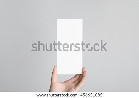 DL Flyer Mock-Up - Male hands holding a blank flyer on a gray background. #456651085