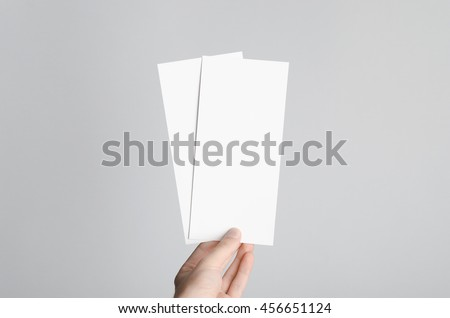 DL Flyer Mock-Up - Male hands holding blank flyers on a gray background. #456651124