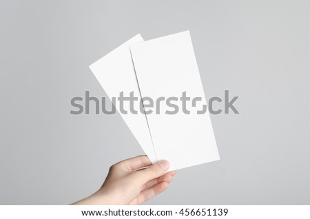 DL Flyer Mock-Up - Male hands holding blank flyers on a gray background. #456651139