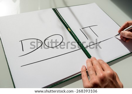 Do It concept with the hand of a man writing the words in large capital letters across an open notebook conceptual of - do not procrastinate, do it immediately.