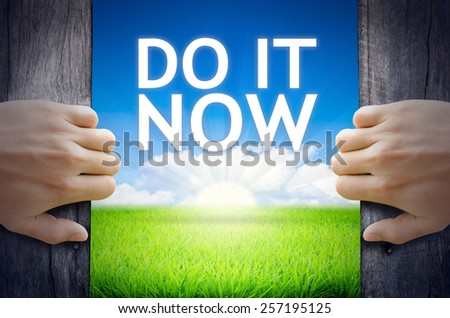 Do it Now. Hand opening an old wooden door and found Do it Now word floating over green field and bright blue Sky Sunrise.