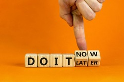 Do it now symbol. Businessman hand turns cubes and changes words 'do it later' to 'do it now'. Beautiful orange background. Business and do it now concept. Copy space.