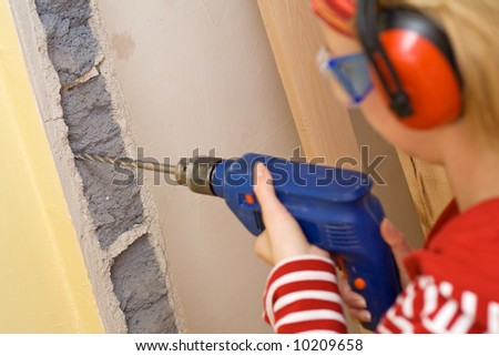 Do it yourself concept - woman drilling a hole into a jagged wall
