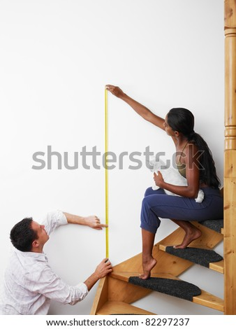 Do it yourself: couple measuring wall to hang picture at home. Vertical shape, copy space