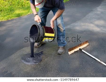 Do it yourself home maintenance. Driveway resealing repair. Homeowner pours blacktop sealant onto driveway #1149789647