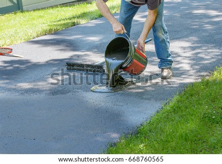 Do it yourself home maintenance. Driveway resealing repair. Homeowner pours blacktop sealant onto driveway