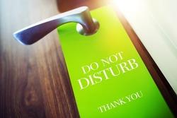 Do Not Disturb Green Paper Hotel Door Hanger. Pleasure Stay in Hotel Concept. Travel Concept.