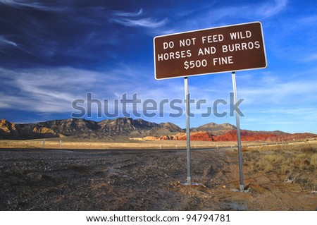Do not feed wild horses sign in beautiful desert landscape