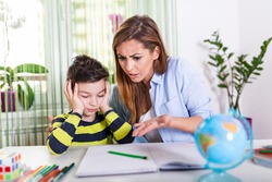 Do not ignore me when I am talking. Moms helping with homework. Mom is angry because her son dont want to do homework. Stressed mother and son frustrated over failure homework.