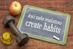 Do not make resolutions, create habits - advice on a vintage slate blackboard with a dumbbell