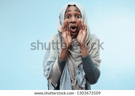 Do not miss. Young casual african woman shouting. Shout. Crying emotional woman screaming on blue studio background. Human emotions, facial expression concept. Trendy colors