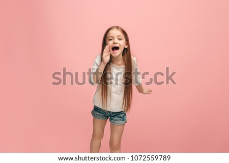 Do not miss. Young casual teen girl shouting. Shout. Crying emotional teenager screaming on pink studio background. Female half-length portrait. Human emotions, facial expression concept. Trendy #1072559789