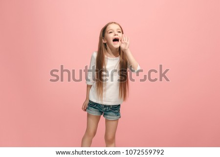 Do not miss. Young casual teen girl shouting. Shout. Crying emotional teenager screaming on pink studio background. Female half-length portrait. Human emotions, facial expression concept. Trendy #1072559792