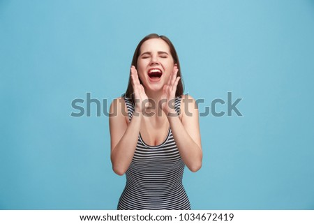 Do not miss. Young casual woman shouting. Shout. Crying emotional woman screaming on blue studio background. Female half-length portrait. Human emotions, facial expression concept. Trendy colors #1034672419