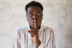 Do not tell anybody. Mysterious young African male looking up, holding fore finger on his lips, saying shh, asking to be quiet, keep silent, sharing secret with you. Consipracy and secrecy concept