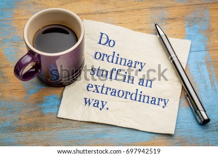Do ordinary things in an extraordinary way - motivational handwriting on a napkin with a cup of espresso coffee #697942519
