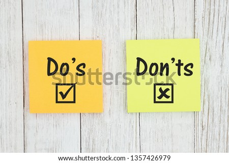 Do's and Don'ts for grammar on two sticky notes  on weathered whitewash textured wood Foto stock ©