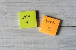 Do's and Don'ts for grammar on two sticky notes on white wooden background.