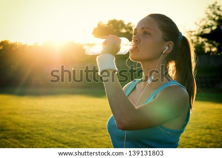 Do Sport in the sunset Young woman drinking water after run