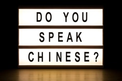 Do you speak Chinese light box sign board on wooden table.