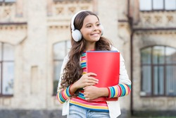 Do you speak english. Happy child listening to English audio course. Little girl learning English with audio book. Improve your English with audio lessons.