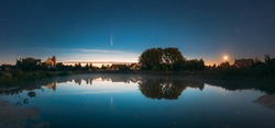 Dobrush, Belarus. Comet Neowise C2020f3 Anf Rising Moon In Night Starry Sky Reflected In Small Lake Waters