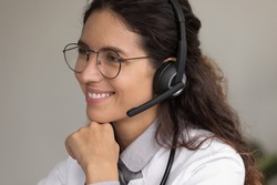 Doc speaking. Friendly young hispanic woman medical consultant gp wear glasses modern wireless headphones take patients calls. Smiling female doctor healthcare helpline worker ready to assist online