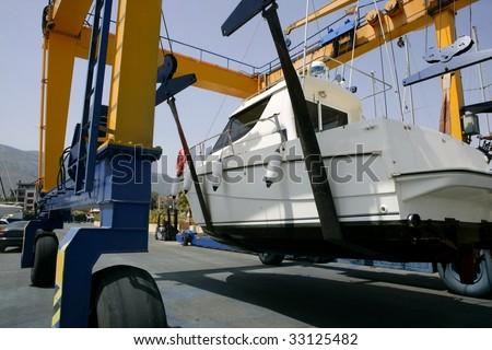 Dock crane elevating a fishing boat in Mediterranean marina
