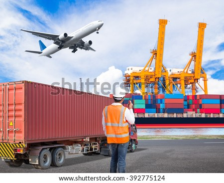 Dock worker talking with radio for controlling loading container in an industrial harbor with truck transport container and cargo plane flying above ship port for logistic import export concept