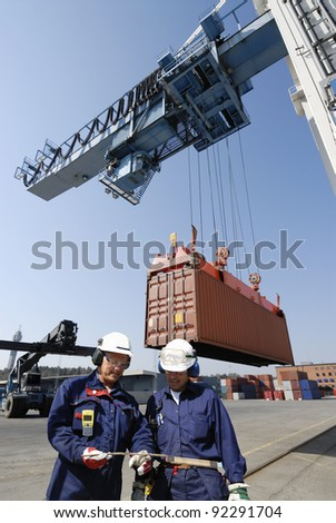 dock workers in container-port cranes and trucks inside commercial dock.