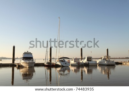 Docked boats in a harbor. Dawn - stock photo