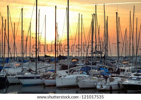 Docked yachts at sunset background