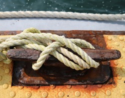 Docking line around a rusty cleat on a pier.