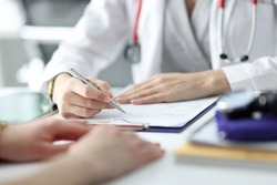 Doctor advising patient and writing in documents closeup. High quality medical care concept