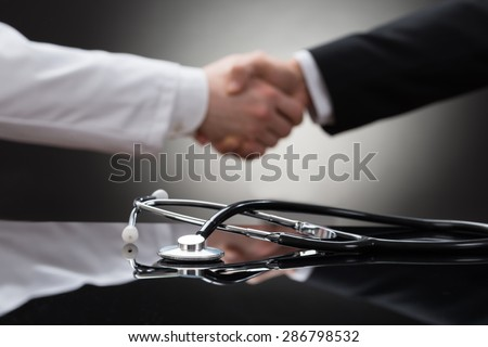 Doctor And Businessman Shaking Hand In Front Of Stethoscope