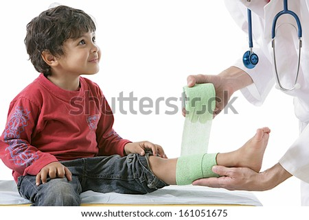doctor and his little patient bandaging of the legs with elastic bandage